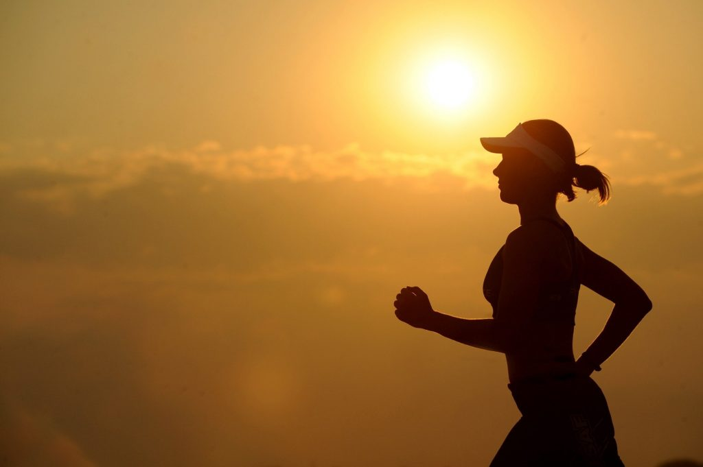 Woman running in front of sunset